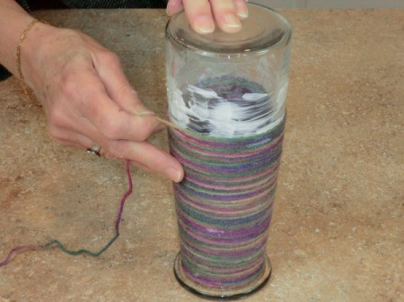 Wrapping yarn around a glass vase.