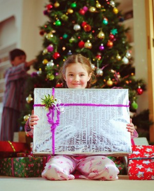 A girl with a present on Christmas morning.