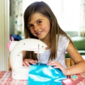 A girl sewing with a sewing machine.