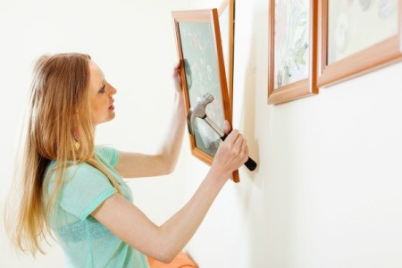 A woman hanging pictures frames on a wall.