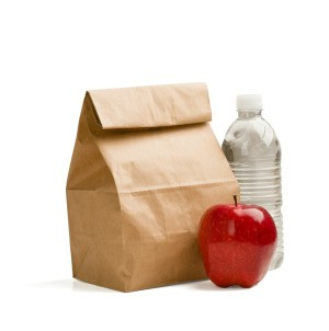 A bagged lunch, bottle of water and a red apple.