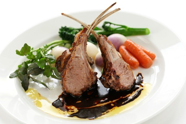 A plate of lamb chops and carrots.