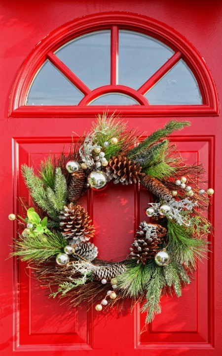 A Christmas wreath on a red door.