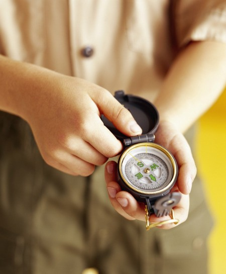 A boy scout looking at a compass.
