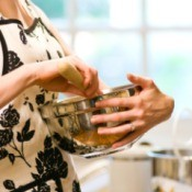 A woman wearing an apron mixing cookies.