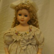 Doll in fancy dress with hair bow.