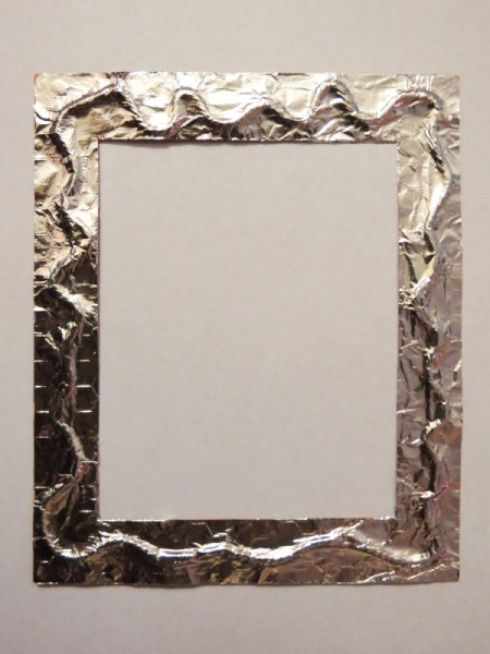 Foil glued to frame over twine.