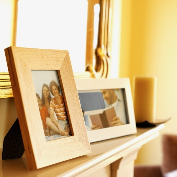 Framed family photos sitting on a shelf.