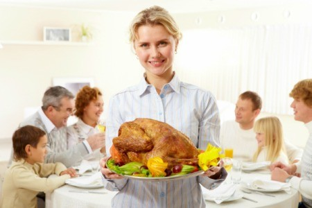 A woman holding a turkey for her family at Thanksgiving.