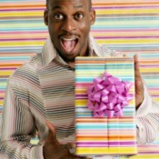 A 30 year old man holding a gift.