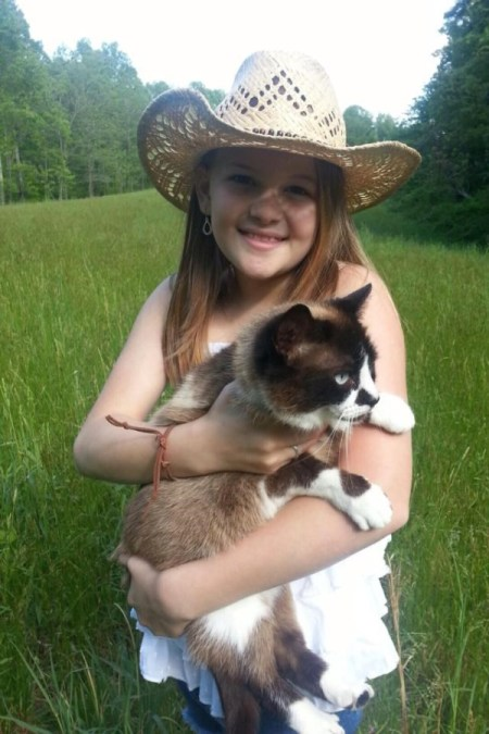 Young girl holding cat.