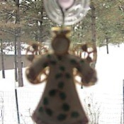 angel pin hanging on window