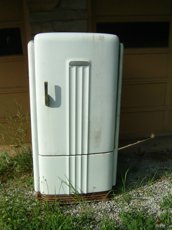 Old worn white metal refrigerator.