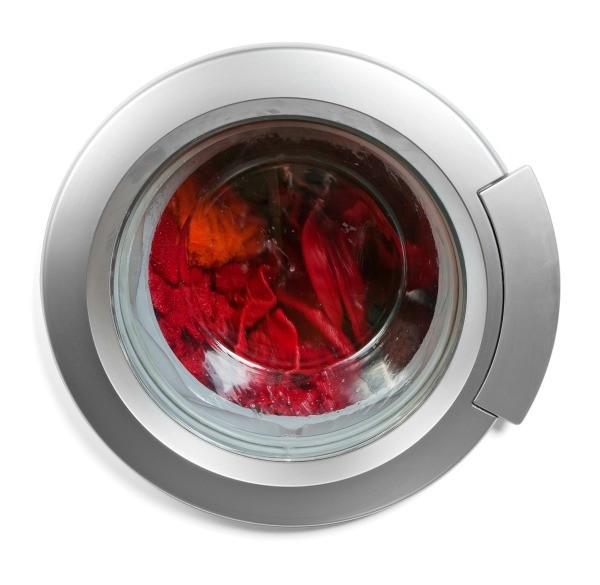 A load of red dyed clothing in a front loader washing machine.