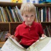 A young boy reading a large book.