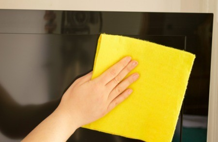 Cleaning a flat screen TV with a soft cloth.