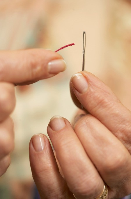 Woman Threading a Sewing Needle