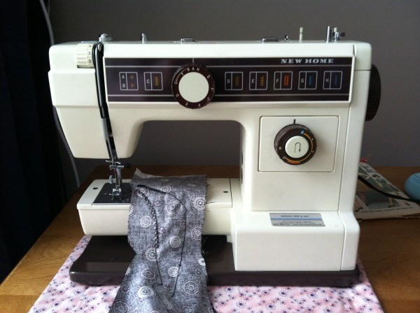 Sewing machine with a piece of fabric on the sewing platform.