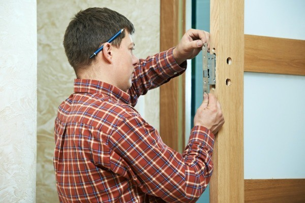 Man Replacing Deadbolt and Door Lock on Door