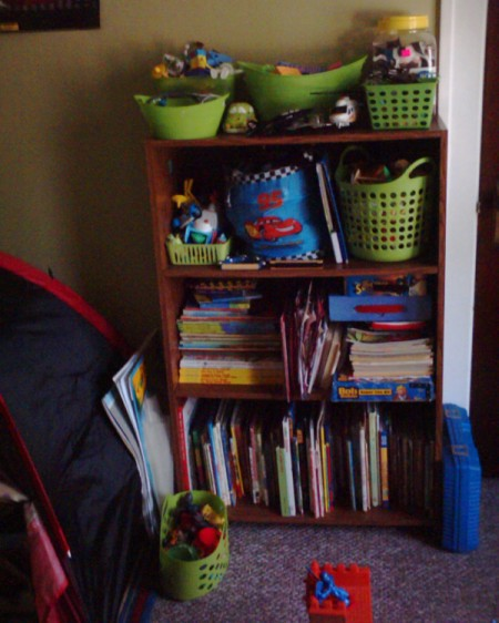 View of child's bookcase and storage bins.