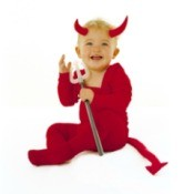 A toddler wearing a devil costume with a tail.