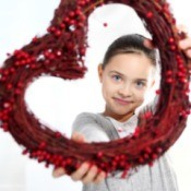 A girl holding a red heart wreath.