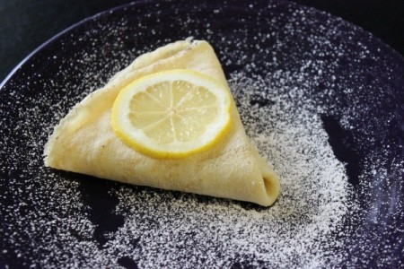 Triangular folded crepe sprinkled with sugar and topped with a lemon slice.
