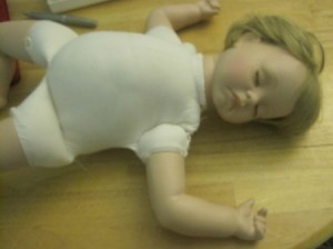 Baby doll lying on its back asleep.