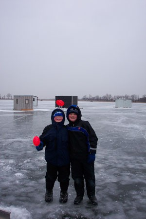 Two people dressed for winter standing on ice covered water.