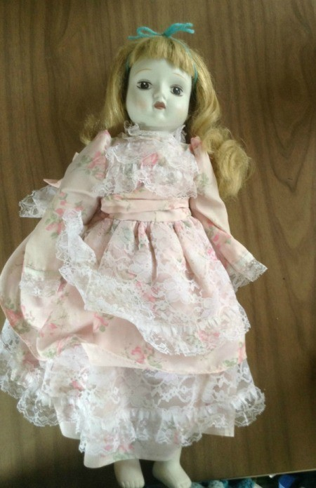 Blond haired porcelain doll with lacy pink dress.