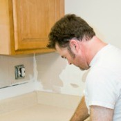 Man repairing kitchen countertops.
