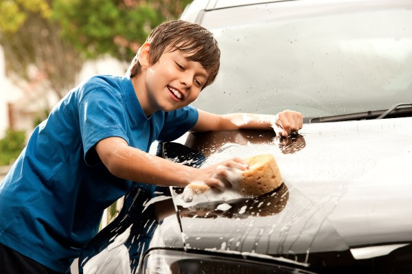 Young teen boy washing the car.