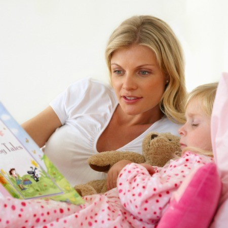A mother reading to her young daughter at bedtime.