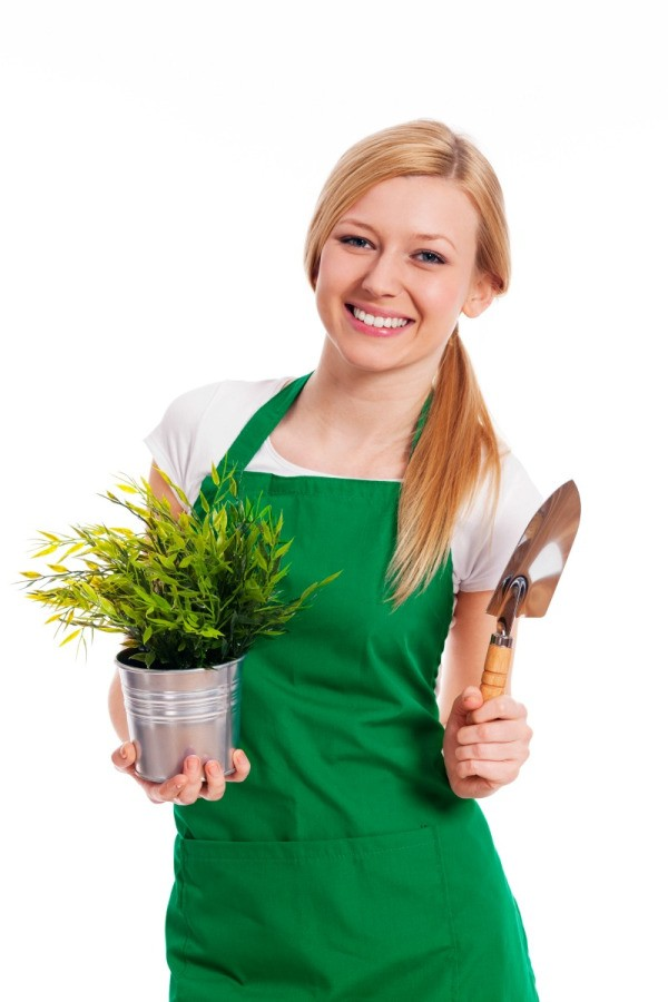 A female gardener wearing a green apron.