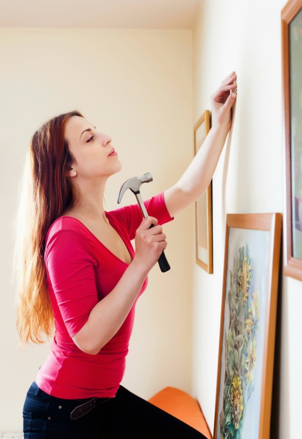 A Woman Hanging Pictures On A Wall Finding The Best Name For Your Handmade Home Decor Business