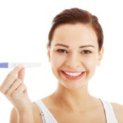 A woman holding a pregnancy test.