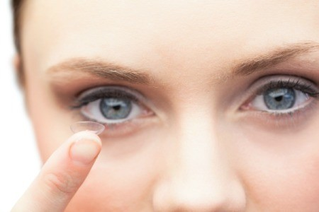 A woman putting on contact lenses.