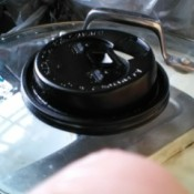A disposable coffee lid being used as a pot scrubber