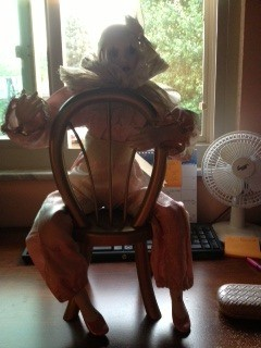 doll sitting backwards on chair