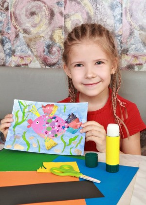 A girl showing off her fish painting.