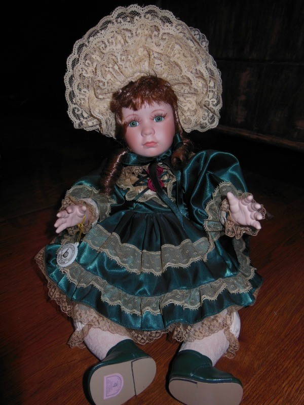 doll in green dress with ecru lace and lacy ruffled hat