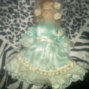 blond doll wearing a blue dress with lace ruffle