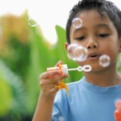 A boy blowing bubbles.