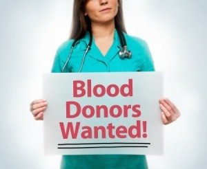 young medical professional holding sign- Blood Donors Wanted