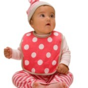 baby wearing a red and white polka dot bib