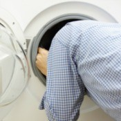 man with head inside front load washer