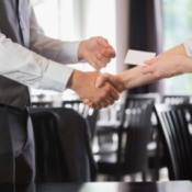 two people shaking hands and exchanging business cards