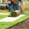 man kneeling to lay lawn sod