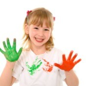 girl with paint on hands from making handprint shirt