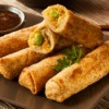 eggrolls on plate with sauce on the side